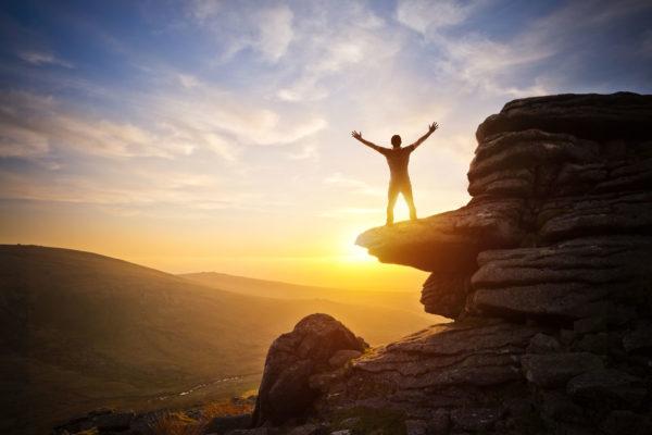 Un homme levant les bras au ciel sur une montagne face au soleil