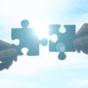 Deux mains tenant chacune une pièce de puzzle