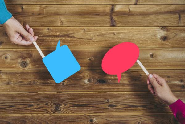 2 mains, celles d'un homme et celle d'une femme tiennent chacune une petite pencarte représentant des bulles de dialogue. celle de l'homme est bleue et de forme carré, celle de la femme est rose et de forme arrondie.